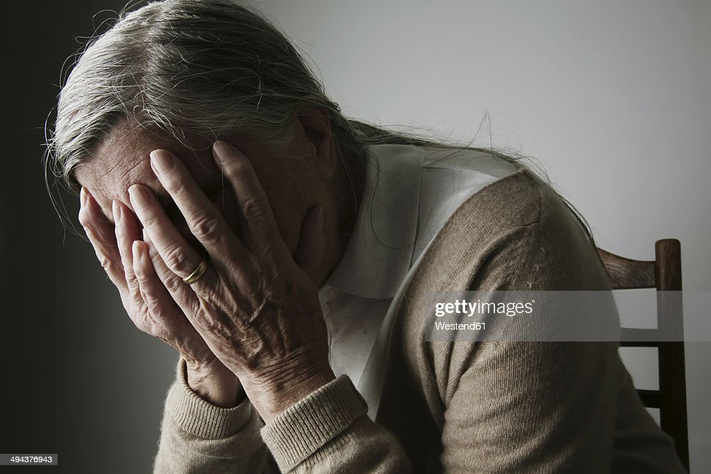 Senior woman covering face with her hands : Stock Photo
