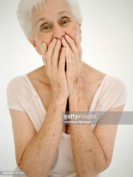 senior woman covering mouth with hands, portrait - keratosis fotografías e imágenes de stock