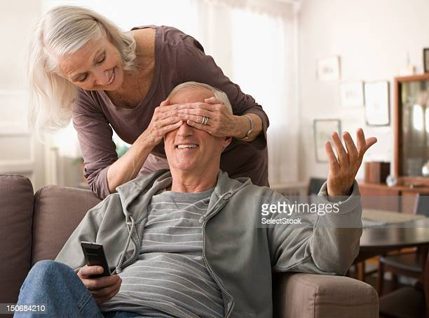 Senior woman covering spouse's eyes