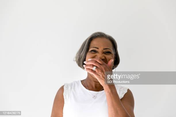 senior woman covers mouth while laughing - hands covering mouth stock pictures, royalty-free photos & images