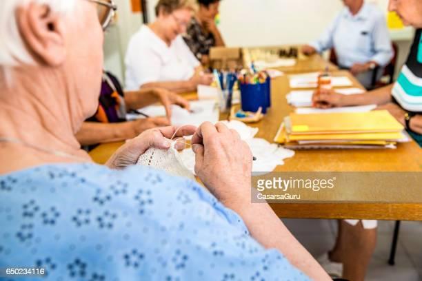 Senior Woman Crocheting At The Community Center