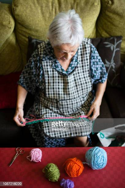 Senior woman crocheting on the couch at home, top view