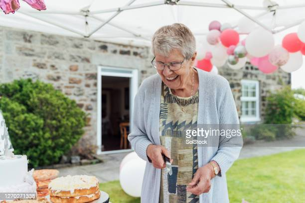 senior woman cutting a cake - letter stock pictures, royalty-free photos & images