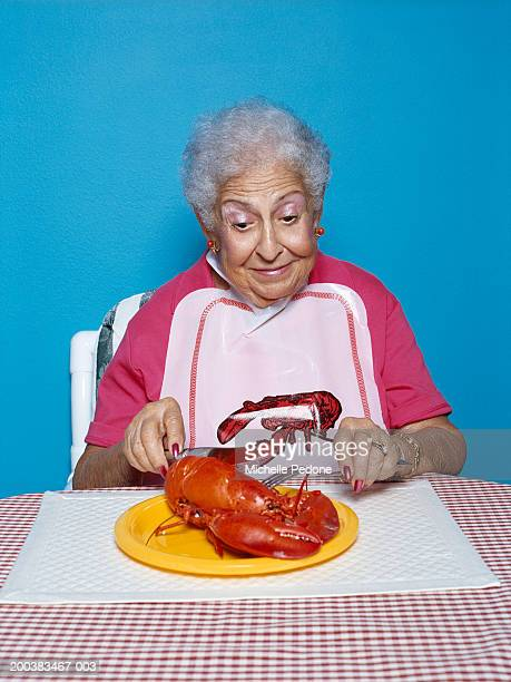 Senior woman cutting lobster with fork and knife, close-up