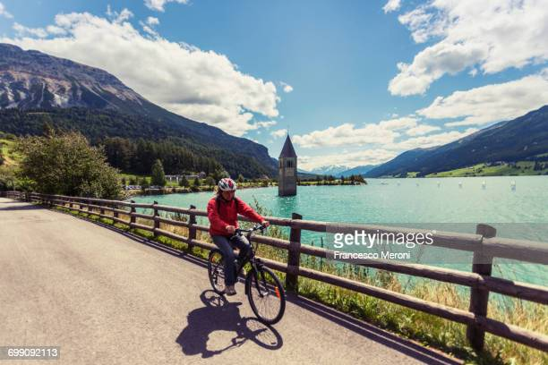 Senior woman cycling by lake with Curon bell tower, Vinschgau Valley, South Tyrol, Italy