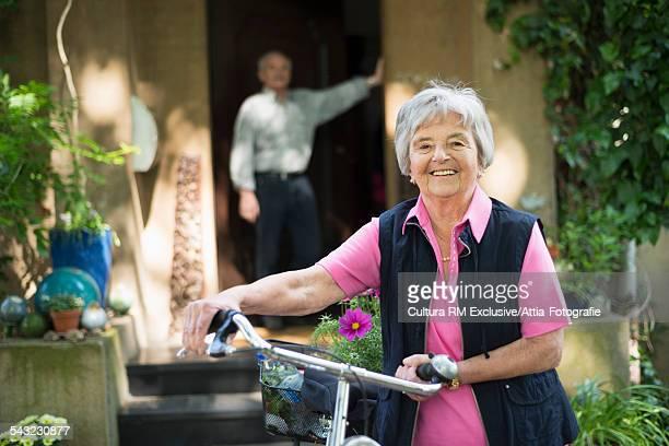Senior woman cyclist and husband at front door