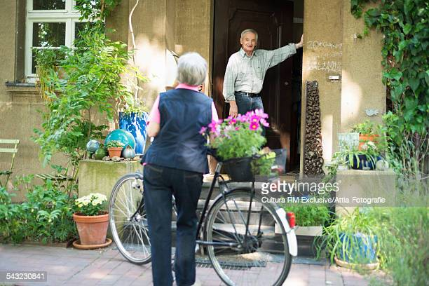 Senior woman cyclist leaving husband at front door