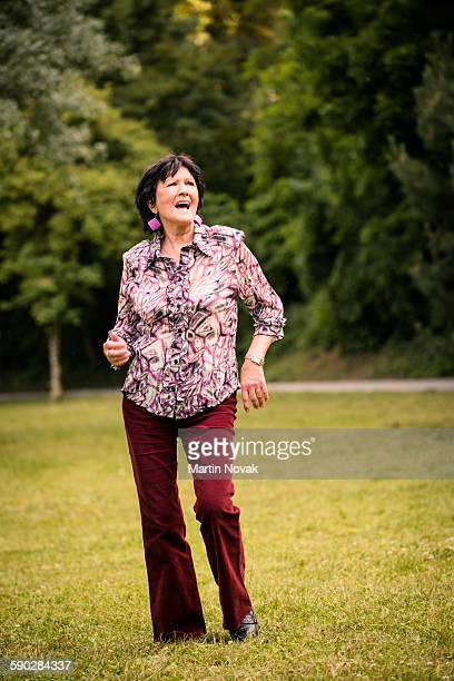 Senior woman dancing on grass outdoor in nature
