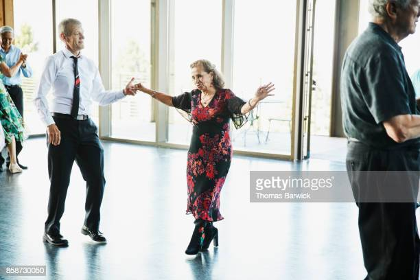 Senior woman dancing with partner in community center
