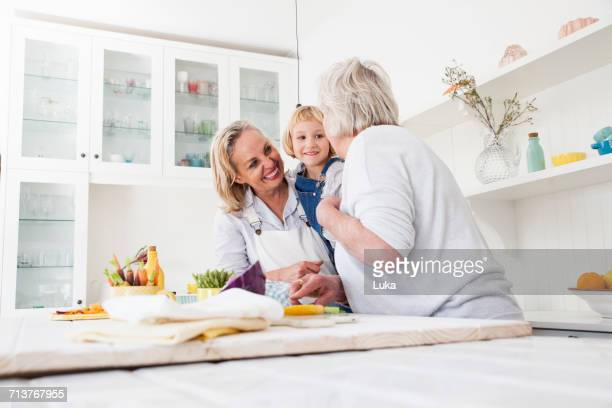 Senior woman, daughter and granddaughter preparing vegetables at kitchen table