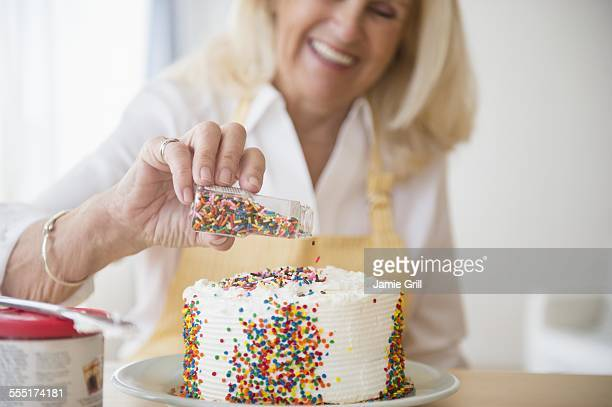 senior woman decorating cake - decorating a cake stock pictures, royalty-free photos & images