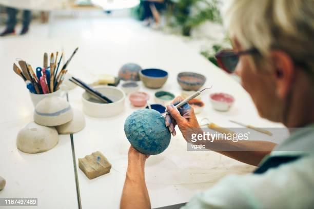 senior woman decorating ceramics bowl at ceramics workshop - craft stock pictures, royalty-free photos & images