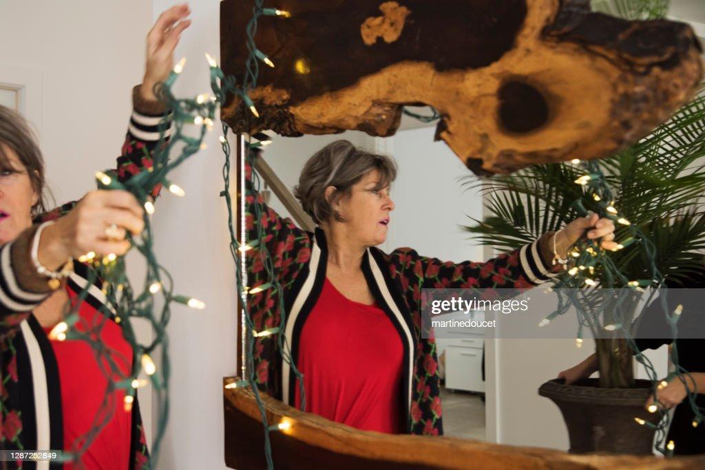 Senior woman decorating with Christmas lights. : Stock Photo