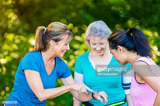 Senior woman demonstrates her sports watch to friends