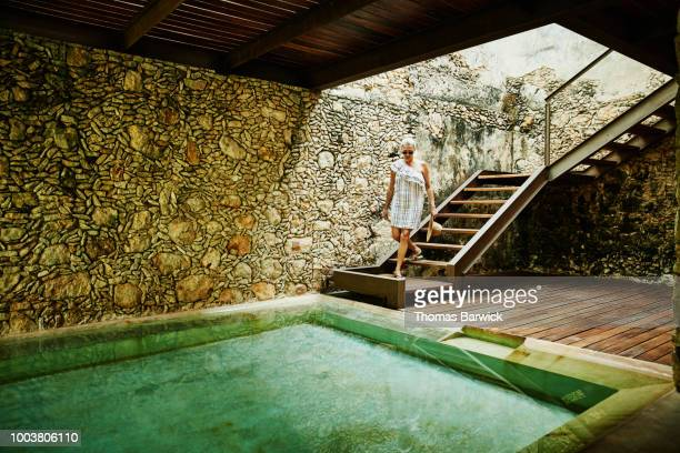 Senior woman descending stairs to spa at luxury resort