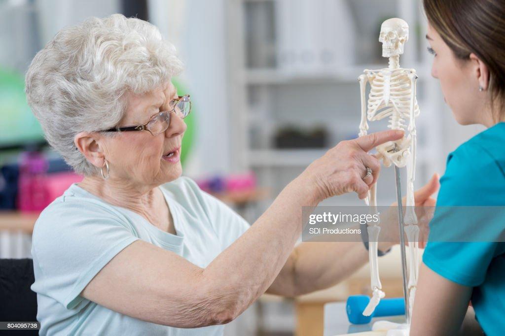 Senior woman describes back pain to therapist : Stock Photo