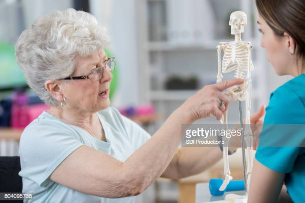 senior woman describes back pain to therapist - osteoporosis stock photos and pictures