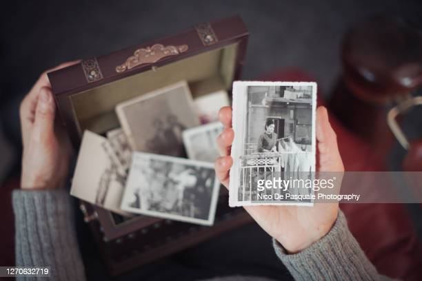 senior woman discovering old photographs - foto stockfoto's en -beelden