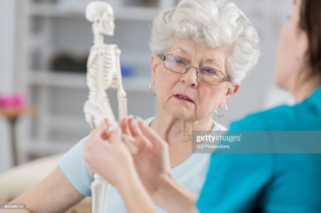 Senior woman discusses posture with physical therapist : Stock Photo