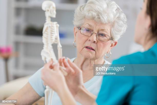 senior woman discusses posture with physical therapist - bones stock photos and pictures