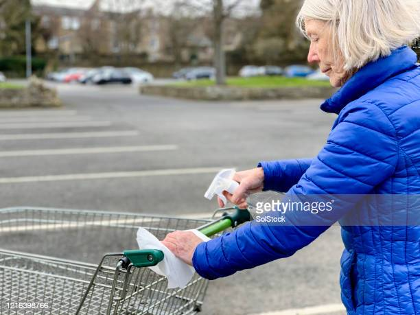 senior woman disinfecting a shopping trolley - state of emergency stock pictures, royalty-free photos & images