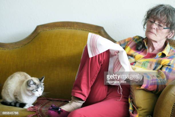 Senior woman doing embroidery on sofa with cat