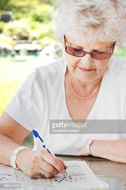 Senior woman doing newspaper crossword puzzle