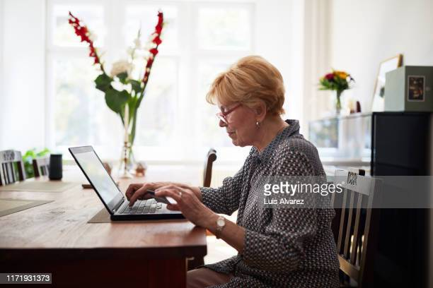 senior woman doing online payment - reading glasses stock pictures, royalty-free photos & images