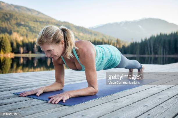 senior woman doing plank on dock near lake during sunset. - plank position stock pictures, royalty-free photos & images