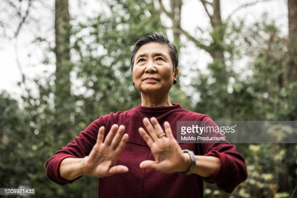 senior woman doing tai chi outdoors - disruptaging stock pictures, royalty-free photos & images