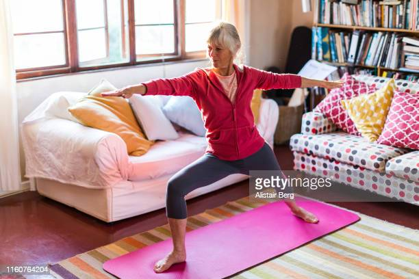 senior woman doing yoga in the living room of her home - relaxation exercise stock pictures, royalty-free photos & images