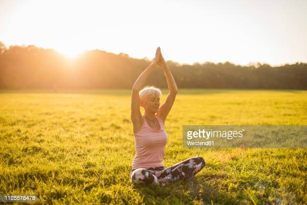 senior woman doing yoga on rural meadow at sunset - adults only stock pictures, royalty-free photos & images