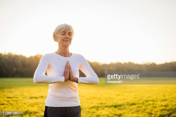 senior woman doing yoga on rural meadow at sunset - young at heart stock pictures, royalty-free photos & images