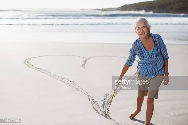 Senior woman drawing heart in sand