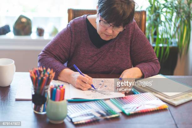 senior woman drawing in adult coloring book in her home - colouring book stock photos and pictures