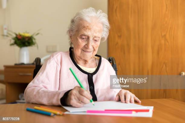 Senior woman drawing on white paper