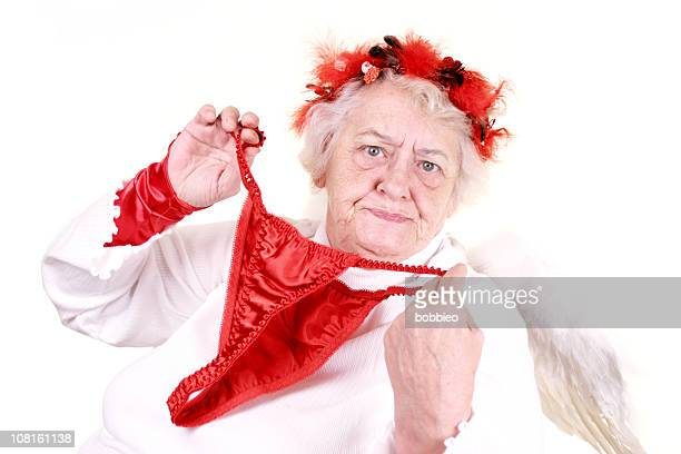 senior woman dressed as cupid and holding panties up - funny cupid stock pictures, royalty-free photos & images