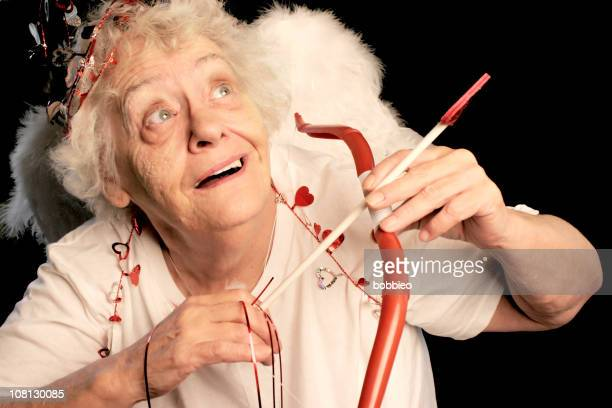 senior woman dressed as cupid with bow and arrow - funny cupid stock pictures, royalty-free photos & images