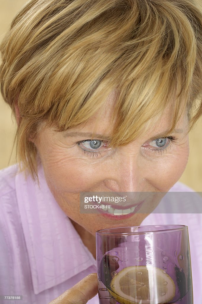 Senior woman drinking a glass of water with lemon : Photo