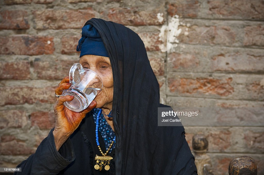 Senior woman drinking clean water in Egypt : Stock Photo