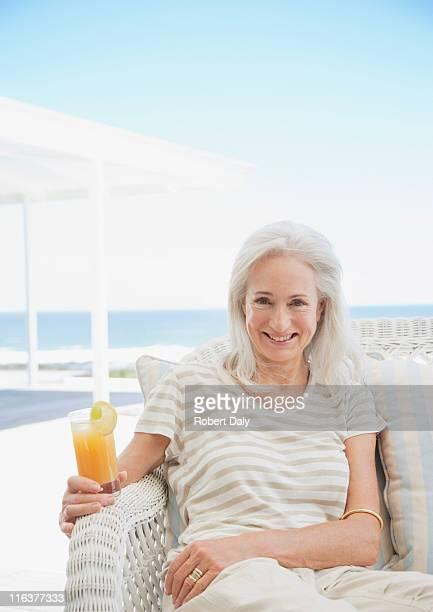 Senior Frau trinkt cocktail auf der Terrasse