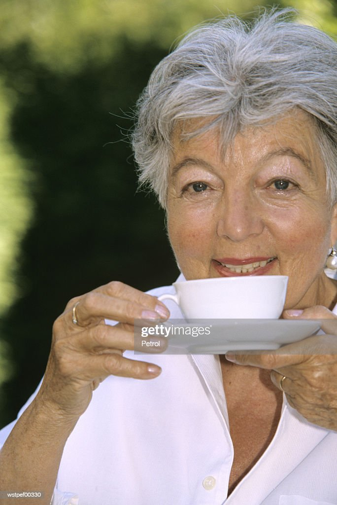 Senior woman drinking coffee, close up : Stock Photo