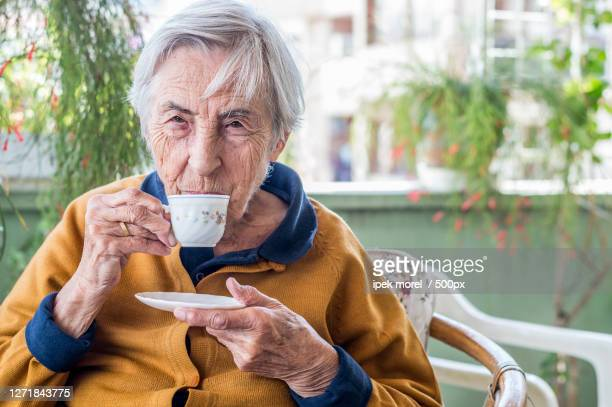 senior woman drinking coffee in cafe, zmir, turkey - ipek morel stock pictures, royalty-free photos & images