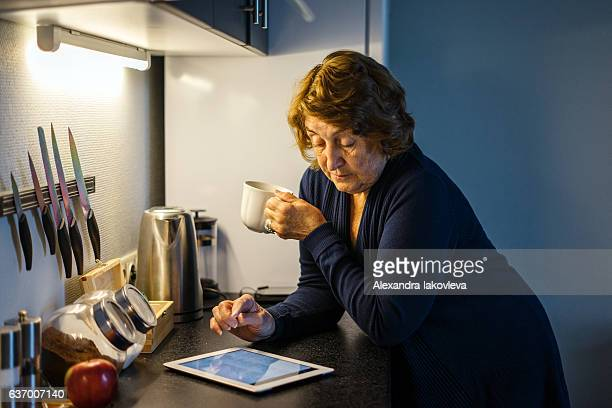 Senior woman drinking coffee while using tablet in her kitchen