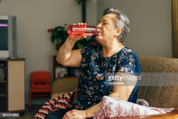 senior woman drinking from a water bottle - thirsty stock pictures, royalty-free photos & images