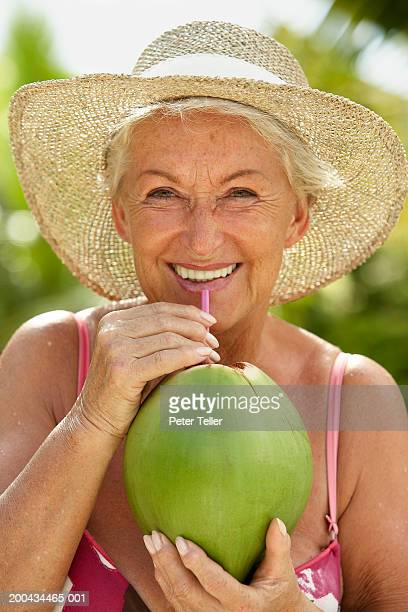 Senior woman drinking from coconut shell, smiling, close up, portrait