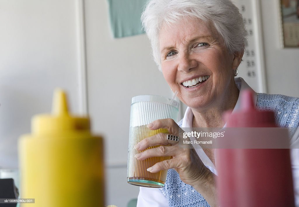 Senior woman drinking ice tea in diner : Foto stock