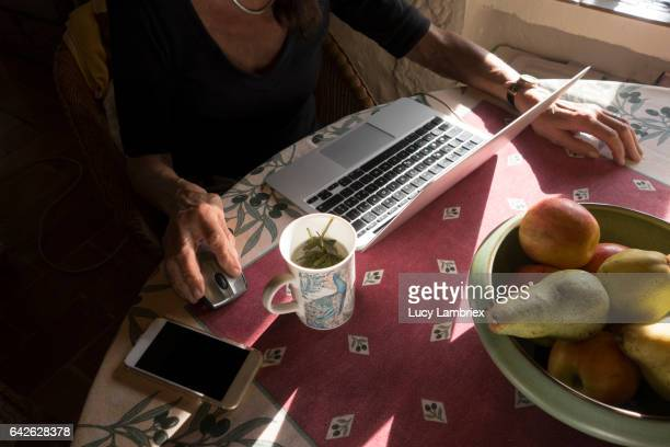 Senior woman drinking tea and working on her laptop