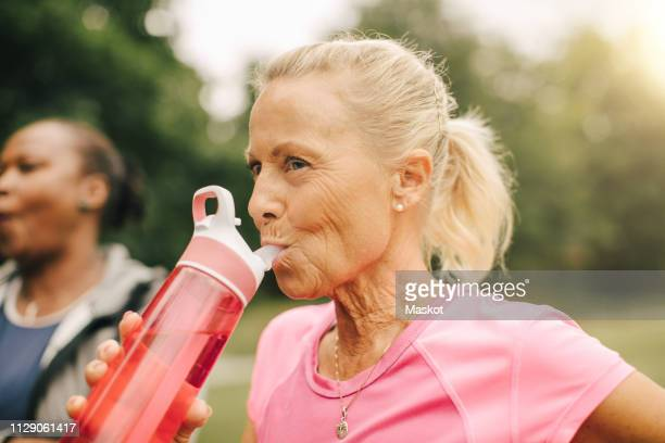 Senior woman drinking water from bottle in park