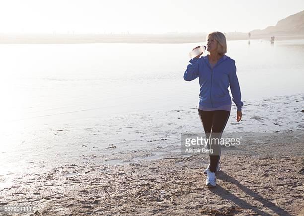 Senior woman drinking water on beach